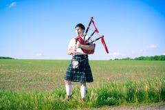 Le portrait de l'homme appréciant jouant siffle dans l'écossais Photographie stock libre de droits