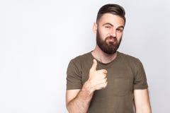 Le portrait de l'homme barbu satisfaisant avec des pouces se lèvent et T-shirt vert-foncé sur le fond gris-clair Images stock