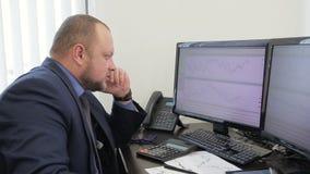 Le portrait de l'homme d'affaires qui appelle à son courtier regardant les diagrammes sur les écrans banque de vidéos