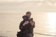 le portrait de l'homme et le chien font le selfie sur le téléphone portable Photo stock