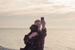 le portrait de l'homme et le chien font le selfie sur le téléphone portable image stock