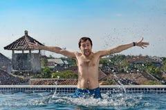 Le portrait de l'homme mince joyeux avec des cheveux de coffre, émerge de la piscine, l'eau éclabousse, montre la langue et les m Images libres de droits