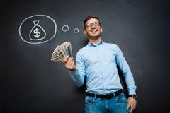 Le portrait de l'homme occupé tenant des dollars remet dedans le tableau noir Image stock