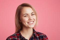 Le portrait de la belle femelle gaie a le large sourire brillant, habillé dans la chemise à carreaux occasionnelle, exprime des é Photo libre de droits