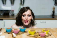 Le portrait de la belle fille avec le maquillage tient des petits gâteaux dans des mains photos libres de droits