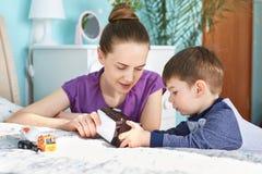 Le portrait de la belle jeune mère joue avec le petit mâle KIS, lui dit que quelque chose intéressante au sujet de la voiture de  image stock