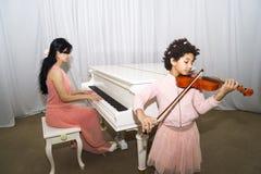Le portrait de la belle obscurité heureuse a pelé la petite fille à l'aide d'un violon tout en jouant une mélodie photographie stock libre de droits