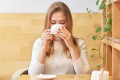 Le portrait de la boisson chaude sirotante femelle calme positive en café avec l'intérieur élégant en bois, tient la tasse dans d image stock