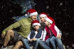 Le portrait de la famille amicale dans Santa couvre regarder l'appareil-photo la soirée de Noël Photos libres de droits