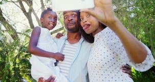 Le portrait de la famille mignonne prend le selfie dans le jardin clips vidéos