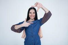 Le portrait de la femelle positive de jeune brune avec l'expression gaie, habillé dans des jeans habillent, ont la bonne humeur,  images libres de droits