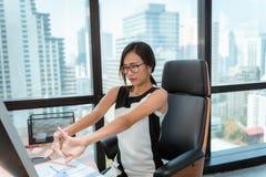 Le portrait de la femme asiatique étire ses mains tout en travaillant à son espace de travail de bureau, soins de santé et concep photographie stock