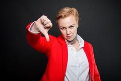 Le portrait de la femme attirante d'affaires montrant le pouce font des gestes vers le bas Photographie stock libre de droits