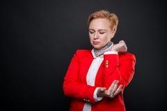 Le portrait de la femme attirante d'affaires tenant le coude aiment blesser Image stock