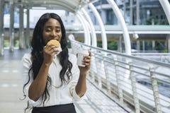 Le portrait de la femme de couleur heureuse d'affaires mange sur les aliments de préparation rapide ha de prise Photos libres de droits