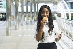 Le portrait de la femme de couleur heureuse d'affaires mange sur les aliments de préparation rapide de prise Photo libre de droits