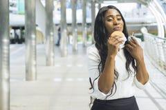 Le portrait de la femme de couleur heureuse d'affaires mange sur les aliments de préparation rapide de prise Photos stock