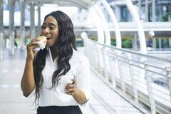 Le portrait de la femme de couleur heureuse d'affaires mange sur les aliments de préparation rapide de prise Images stock