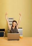 Le portrait de la femme d'affaires avec des bras a augmenté, tasse et ordinateur portable sur le bureau Photo stock