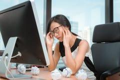 Le portrait de la femme d'affaires ayant le mal de t?te pendant le fonctionnement dans le lieu de travail de bureau, femme asiati photos libres de droits