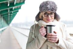 Le portrait de la femme de sourire dans la participation chaude d'habillement a isolé le récipient de boissons photographie stock