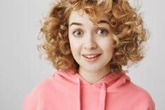 Le portrait de la femme européenne enthousiaste étonnée avec grésillent coiffure, souriant avec les sourcils soulevés, exprimant images libres de droits