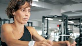 Le portrait de la femme fait des exercices pour des muscles d'épine sur la machine à ramer banque de vidéos