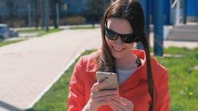 Le portrait de la femme heureuse d'oung dans le manteau rouge attend quelqu'un et vérifie son téléphone, textotant banque de vidéos