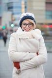 Le portrait de la femme heureuse dans des bras debout d'habillement chaud a croisé sur la rue de ville images stock