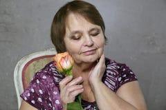 Le portrait de la femme supérieure heureuse tenant l'orange s'est levé Photos stock