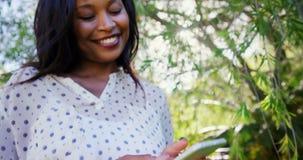 Le portrait de la femme utilise le smartphone et sourit dans le jardin clips vidéos