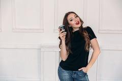 Le portrait de la fille étonnante dans un studio léger boit du café Un modèle merveilleux avec les cheveux bouclés et les lèvres  Image stock
