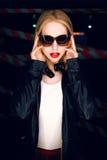 Le portrait de la fille blonde sexy avec les lèvres rouges portant une roche noircissent le style sur le fond du dispositif avert Photos libres de droits