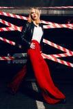 Le portrait de la fille blonde sexy avec les lèvres rouges portant une roche noircissent le style sur le fond du dispositif avert Photo stock