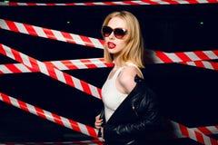 Le portrait de la fille blonde sexy avec les lèvres rouges portant une roche noircissent le style sur le fond du dispositif avert Images stock