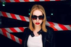 Le portrait de la fille blonde sexy avec les lèvres rouges portant une roche noircissent le style sur le fond du dispositif avert Image libre de droits