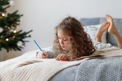 Le portrait de la fille bouclée adorable passe le temps gratuit sur le lit, fait la carte de Noël pour des parents, écrit des sou photographie stock