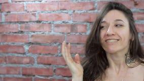 Le portrait de la fille d'une chevelure foncée masculine dépeignent la surprise in camera Mur de briques banque de vidéos
