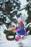 Le portrait de la fille dans la fille de for?t d'hiver porte un arbre et des pr?sents de No?l avec le tra?neau images stock