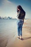 Le portrait de la fille de brune dans des vêtements sport marche par la rivière Photographie stock