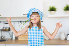 Le portrait de la fille de sourire dans le cuisinier vêtx des amusements à l'oignon de groupe sur une cuisine Images libres de droits