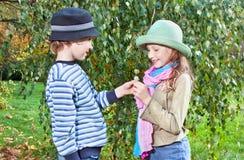 Le portrait de la fille heureuse et le garçon appréciant l'automne d'or assaisonnent Images stock