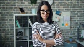 Le portrait de la fille indépendante dans le bureau avec des bras a croisé regarder la caméra banque de vidéos