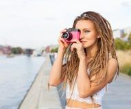 Le portrait de la fille à la mode avec redoute et de l'appareil-photo de vintage se tenant prêt la rivière Concept moderne de mod Images stock