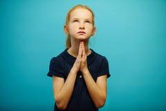 Le portrait de la fille rousse a plié ses mains dans des mains et recherche, exprime un désir sincère d'accomplir le rêve ou de l photo libre de droits