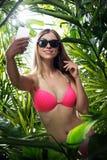 Le portrait de la gentille jeune femme accroche dans tropical Photos stock