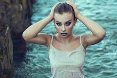 Le portrait de la jeune belle femme avec provocateur composent la position dans l'eau de mer sous la pluie et toucher ses cheveux images stock
