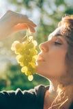 Le portrait de la jeune belle femme tenant des raisins, veut manger la fraise, sur la nature verte d'été de fond, coucher du sole Photo stock