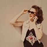 Le portrait de la jeune belle fille bouclée de brune dans des lunettes de soleil avec les lèvres rouges parlant le téléphone fait Photographie stock libre de droits
