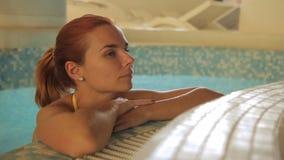 Le portrait de la jeune dame qui se tient dans la piscine près du conseil dans le salon de luxe de station thermale banque de vidéos